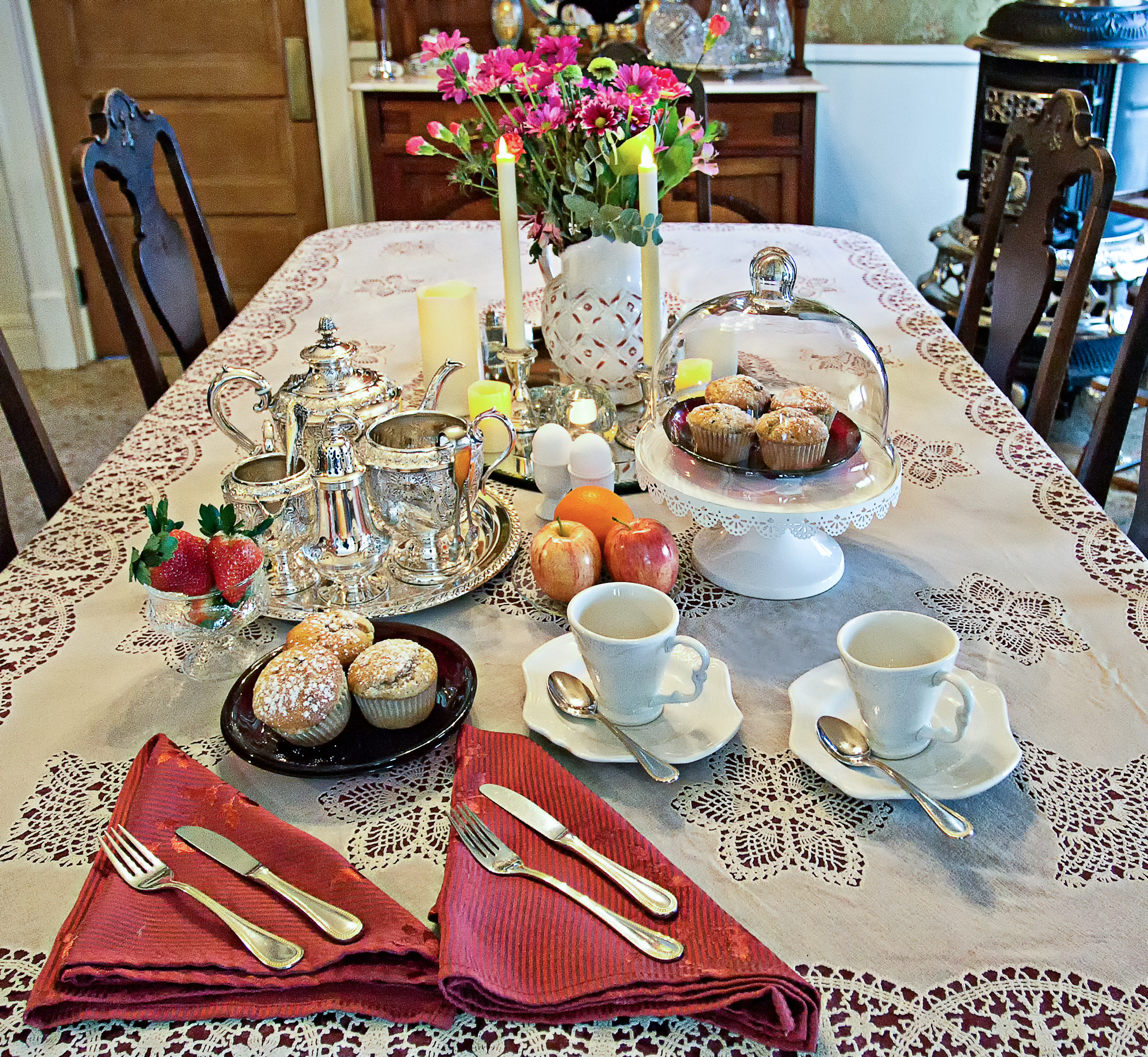 Picture of the breakfast table with food and flowers in the middle.