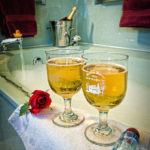 Picture of two wine glasses with a bathtub in the background.