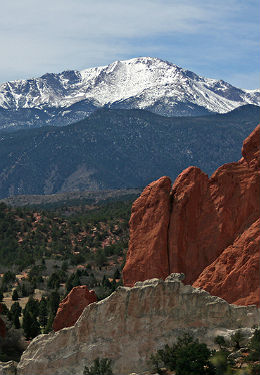 Snow covered Pikes Peak with green brush below and red rock in the foreground