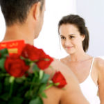 Picture of roses in the foreground with a man looking at a women in the background.